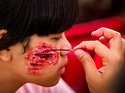 "13 JANUARY 2018 - BANGKOK, THAILAND:      A Thai army nurse uses theatrical makeup to put a simulated combat wound on a girl during Children's Day activities at the Royal Thai Army's King's Guard 2nd Cavalry Camp in central Bangkok. Children's Day is called ""Wan Dek"" in Thai. Many government offices and military bases hold special activities for children as do shopping malls.  PHOTO BY JACK KURTZ"