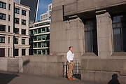 A businessman enjoys a quiet cigarette outside office buildings during an unusual autumn heatwave on 13th September 2016, in the City of London, England.