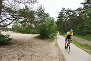 In Soest rijdt een man op een racefiets langs de Soesterduinen.<br /> <br /> In Soest a man is cycling on a road bike.