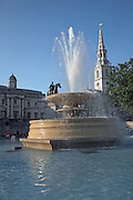 Water fountain, statue, Trafalgar Square, London, England with Saint Martin in the Fields church