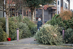 © Licensed to London News Pictures. 07/01/2021. London, UK. A woman walks between piles of Christmas tress at a recycling point in Kensal Green, West London, which haven't been collected during a third national Lockdown. Photo credit: Ben Cawthra/LNP