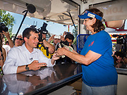 """13 AUGUST 2019 - DES MOINES, IOWA: PETE BUTTIGIEG pays for a """"pork chop on a stick"""" he bought at the Iowa State Fair. Buttigieg, the Mayor of South Bend, Indiana, is running to be the Democratic nominee for the US presidency. He spoke at the Des Moines Register Political Soap Box at the Iowa State Fair and then toured the fairgrounds. Iowa has the first event of the presidential selection cycle. The Iowa Caucuses are February 3, 2020.               PHOTO BY JACK KURTZ"""