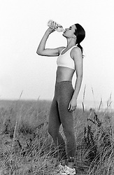 Athletic woman drinking water at the beach