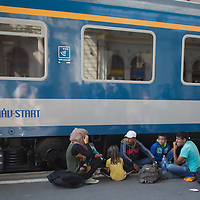 Illegal migrant family sits on the platform as they wait to board a train in hopes to leave for Germany at the main railway station Keleti in Budapest, Hungary on September 03, 2015. ATTILA VOLGYI