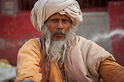 Portrait of an old Indian man with traditional attire and beard staring at camera