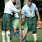 August 18, 2007 -- BRUNSWICK, Maine.  Master Caber throwers, Mike Zolkewicz, right, and Steve Graham, help Connor Dyer, 15, of Westbrook, balance the training caber after the competition at the Maine Highland Games at Thomas Point Beach in Brunswick, Photo by Roger S. Duncan.