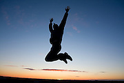 A man jumps with joy, raising his arms into the air, as the sun sets over the Palouse Valley near Spokane, Washington.