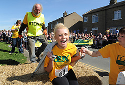 © Licensed to London News Pictures. 06/04/2015. Gawthorpe, UK. A competitor look relieved after crossing the finishing line during the World Coal Carrying Championships, Gawthorpe, West Yorkshire. Photo credit : Anna Gowthorpe/LNP