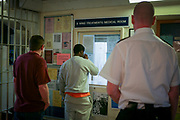 A prison officer watches prisoners as they collect their medication from the B wing treatment room at Wandsworth prison. HM Prison Wandsworth is a Category B men's prison at Wandsworth in the London Borough of Wandsworth, South West London, United Kingdom. It is operated by Her Majesty's Prison Service and is one of the largest prisons in the UK with a population over 1500 people. (photo by Andy Aitchison)