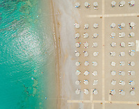 Aerial view of beach lined with thatch parasols, Rhodes island, Greece.
