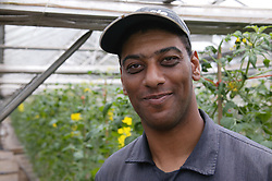 Portrait of man with learning disability standing in greenhouse at Brook Farm; Linby; wearing cap and smiling,