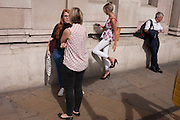A woman commuter adjusts her heels that she's just put on outside the Bank of England in Threadneedle Street on 12th September, in the City of London, UK.