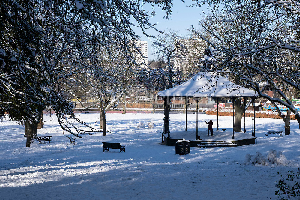 Small figure practices tai chi in the bandstand as part of a winter scene in the snow in Canon Hill Park in Moor Green on 25th January 2021 in Birmingham, United Kingdom. Deep snow arrived in the Midlands giving some light relief and fun during the current lockdown for people who simply enjoyed the weather.