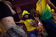Supporters of the Brazilian national team, wearing green and yellow shirts, watch the opening game Brazil vs Croatia and celebrate Brazils victiry, Favela Do Moniho, Sao Paulo, Brazil.