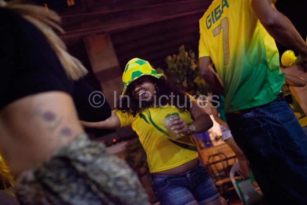 Supporters of the Brazilian national team, wearing green and yellow shirts, watch the opening game Brazil vs Croatia and celebrate Brazils victiry, Favela Do Moniho, Sao Paulo, Brazil.