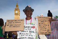 London, June 21st 2017. Protesters march through London from Sheherd's Bush Green in what the organisers call 'A Day Of Rage' in the wake of the Grenfell Tower fire disaster. The march is organised by the Movement for Justice By Any Means Necessary and coincides with the Queen's Speech at Parliament, the destination. PICTURED: A woman's placards condemns the government austerity programme and demand justice for the victims of the Grenfell Tower disaster.