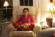 Eleven year old Sofia relaxes in chair to read
