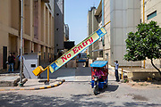 A security guard opens a No Entry barrier for a motor rickshaw to drive out onto the street at TDI Mall on 18th September 2018 in Delhi, India.