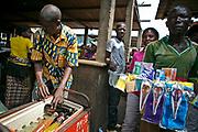 Street vendors selling scissors and beverages walk around in an indoor market in Bangui.