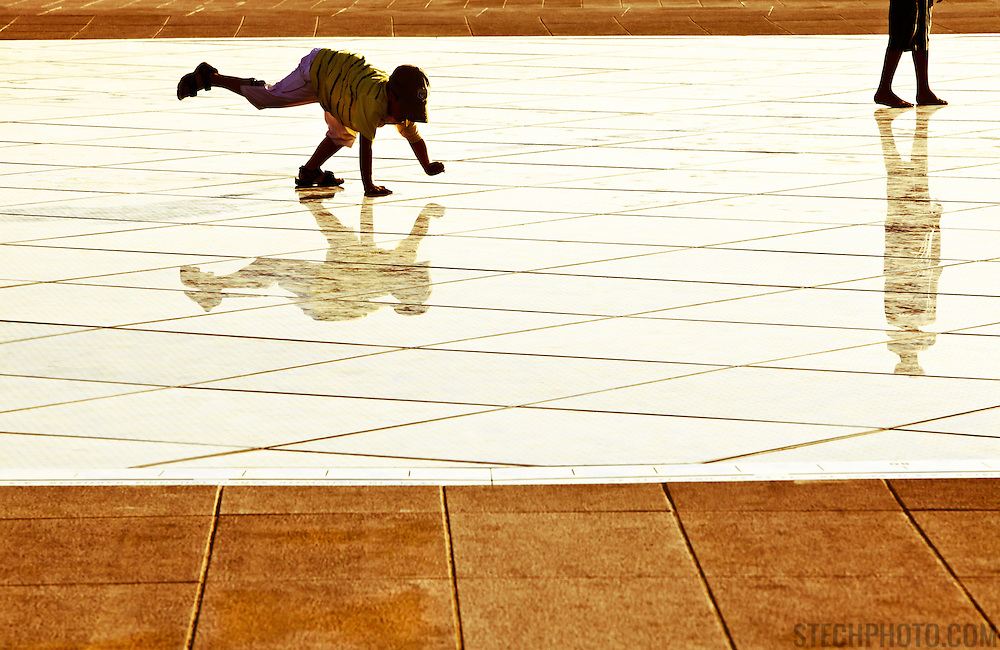 A boy playing on the Sun Salutation solar platform in Zadar, Croatia. Designed by architect Nikola Basic, it harvests sun during the day and puts on a light show in the evening using the rhythm of the waves.