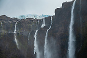 """See multiple waterfalls plunge from Castaño Overo Glacier at Mirador Castaño Overo on Cerro Tronador, an extinct stratovolcano in the southern Andes, near Bariloche, in the Lake District of Argentina, in Patagonia, South America. This viewpoint from a side trail is marked as """"Castaño Overo 1 Hour"""", an easy side trip from the longer path to Otto Meiling Refuge. The sound of falling seracs inspired the name Tronador, Spanish for """"Thunderer."""" With an altitude of 3470 m, Tronador stands more than 1000 meters above nearby mountains in the Andean massif, making it a popular climb in Patagonia, South America. Located inside two National Parks, Nahuel Huapi in Argentina and Vicente Pérez Rosales in Chile, Tronador hosts eight glaciers, which are retreating due to warming of the upper troposphere."""