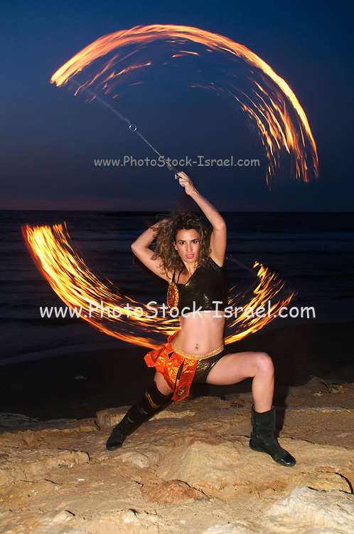 a female fire juggler juggles fire on the beach at sun set