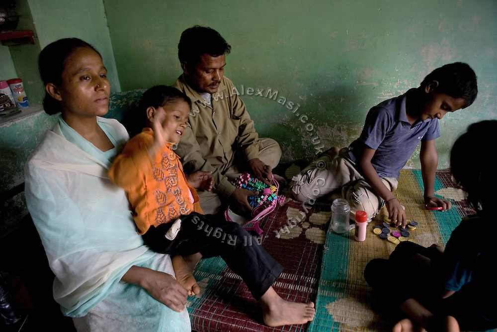 Shafiq Syed, 34, is playing with his three children and wife, (left to right) Nadeem, 4, Waseem, 11, and Simran, 7, in his home located in a poor neighbourhood of Bangalore, Karnataka, India. Shaifq has been the main character of the Cannes' Camera D'Or 1988 winner Salaam Bombay, but after the movie he failed to become a star, fell back into poverty and lived on the streets for years before he became a rickshaw (tuk-tuk) driver in his home city of Bangalore, Karnataka State, India.