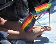A woman holds flags between her toes as the  37th annual Gay Pride Parade passes by in Seattle. The Gay Pride Parade started at Union Street, went north on 4th Avenue, and ended at the Seattle Center.  The sidewalks were packed as tens of thousands attended the parade.<br />