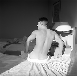 muscular man in bed getting up