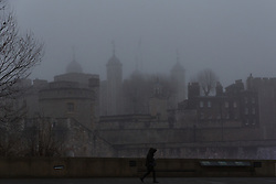 © Licensed to London News Pictures. 30/12/2016. LONDON, UK.  A woman walks past the Tower of London, which is shrouded in fog. London is experiencing more freezing and foggy weather this morning.  Photo credit: Vickie Flores/LNP