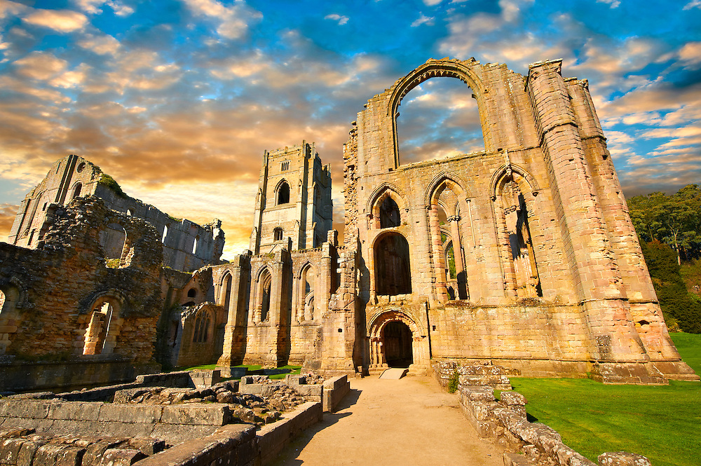 Exterior at sunrise  of the ruins of Fountains Abbey , founded in 1132, is one of the largest and best preserved ruined Cistercian monasteries in England. The ruined monastery is a focal point of England's most important 18th century Water, the Studley Royal Water Garden which is a UNESCO World Heritage Site. Near Ripon, North Yorkshire, England .<br /> <br /> Visit our MEDIEVAL PHOTO COLLECTIONS for more   photos  to download or buy as prints https://funkystock.photoshelter.com/gallery-collection/Medieval-Middle-Ages-Historic-Places-Arcaeological-Sites-Pictures-Images-of/C0000B5ZA54_WD0s