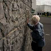 A visitor touches the stone, on a wall in Knock Shrine, where millions believe the Virgin Mary appeared in 1879. Despite the general population showing outrage for the treatment of infants at the hands of local Catholic institutions, and other scandals involving the church, Catholic devotion and  faith is still very prominent in this part of the country.