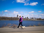 """29 MARCH 2020 - DES MOINES, IOWA: A person walks her dog on an empty trail around Gray's Lake, a popular park and lake near downtown Des Moines, with the city skyline in the background, Sunday. On Sunday morning, 29 March, Iowa reported 336 confirmed cases of the Novel Coronavirus (SARS-CoV-2) and COVID-19. There have been four deaths attributed to COVID-19 in Iowa. Restaurants, bars, movie theaters, places that draw crowds are closed until 07 April. The Governor has not ordered """"shelter in place""""  but several Mayors, including the Mayor of Des Moines, have asked residents to stay in their homes for all but the essential needs. People are being encouraged to practice """"social distancing"""" and many businesses are requiring or encouraging employees to telecommute.        PHOTO BY JACK KURTZ"""