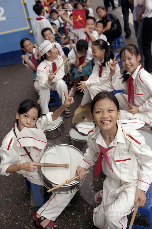 Excited kids participating in a school parade in Hanoi pose for the camera, Vietnam, Southeast Asia