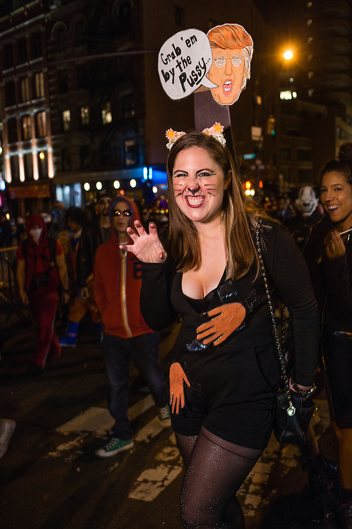 """New York, NY - 31 October 2016. A woman costumed as a cat with a cutout of Donald Trump looming over her, orange hands at her breats and groin, and a voice bubble that reads """"Grab 'em by the Pussy."""""""