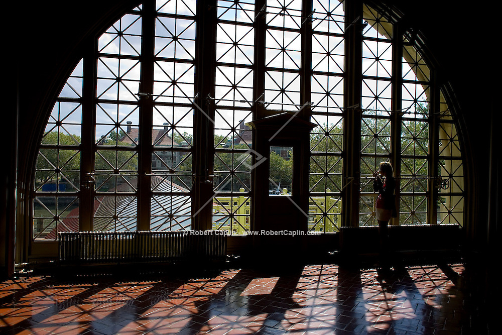 Karen Osate of France gazes through Ellis Island's Registration Hall windows. For Seth Kugle's Weekend in New York Column.  Aug. 3, 2008.