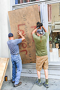 Charleston, South Carolina, USA. 03 September 2019. Workers attach plywood sheets to cover the windows of a shop on historic King Street in preparation for Hurricane Dorian September 3, 2019 in Charleston, South Carolina. The slow moving monster storm devastated the Bahamas and is expected to reach Charleston as a Category 2 by Thursday morning.