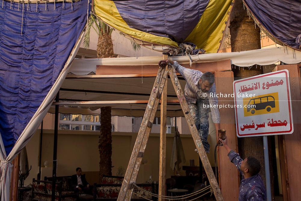 Workmen repair the facade of a restaurant in Luxor, Nile Valley, Egypt.