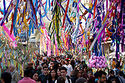 Colourful paper streamers hang in the street with a crowd underneath, very busy street during a Japanese festival in Liberdade, the Japanese district of Sao Paulo, which has the largest diasporah ouside of Japan. Sao Paulo, Brazil.