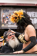 A bearded biker enjoys attention from an exotic dancer on Main Street during the 74th Annual Daytona Bike Week March 7, 2015 in Daytona Beach, Florida.