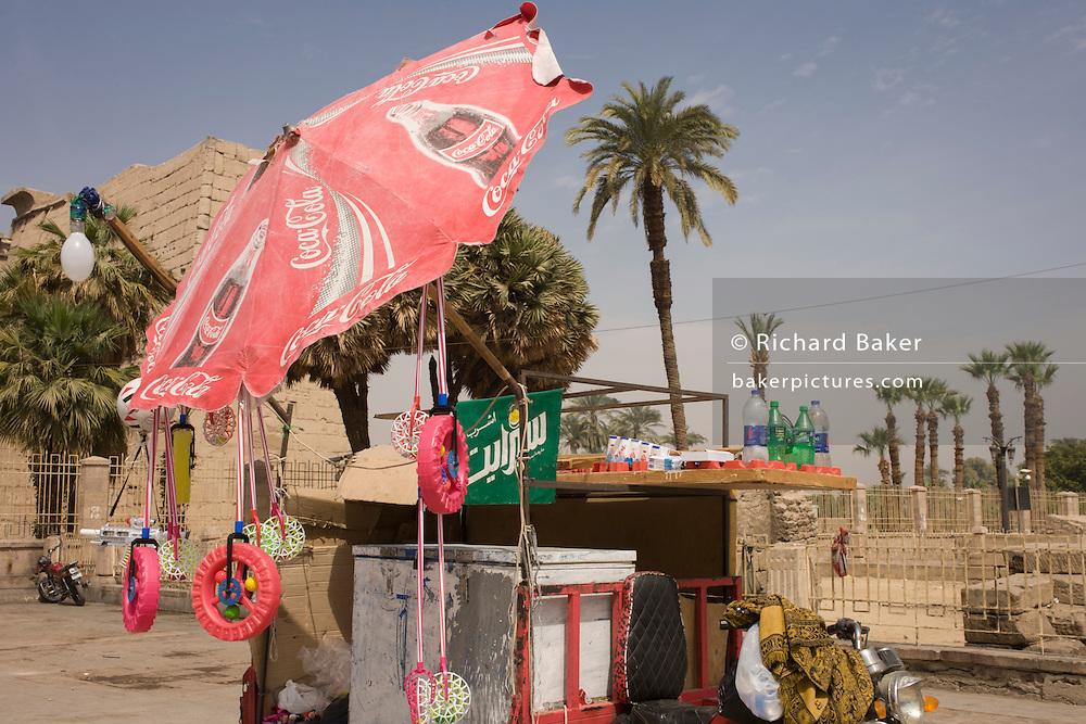 A tourist stall with Coca-Cola umbrella in Luxor Square, Luxor Temple, Nile Valley, Egypt.