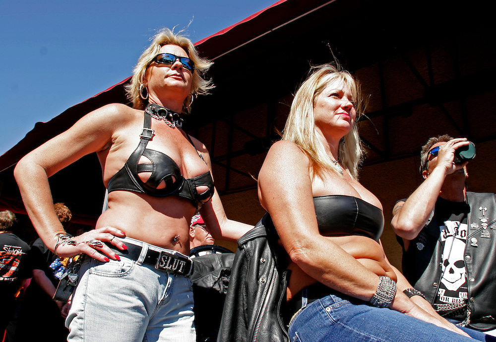 Women watch the constant parade of motorcycles on Main Street during Bike Week in Daytona Beach, Florida March 10, 2005. Bike Week and its associated events attract motorcyclist enthusiasts from around the globe with over 500,000 expected this year.