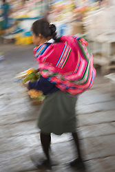 Woman in market with colorful shawl (blurred motion), Cuzco, Peru, South America