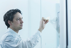 Businessman removing adhesive notes from frosted glass in the office, Freiburg im Breisgau, Baden-Wuerttemberg, Germany