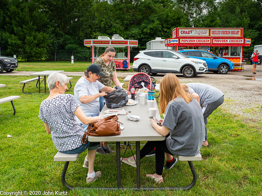 """26 JUNE 2020 - DES MOINES, IOWA: People from Des Moines set up their picnic table after ordering lunch at Fair Food Friday in Des Moines. The 2020 Iowa State Fair, like many state fairs in the Midwest, has been cancelled this year because of the COVID-19 (Coronavirus) pandemic. The cancellation of the fair left many small vendors stranded with no income. Some of the fair food vendors in Iowa started """"Fair Food Fridays"""" on a property a few miles south of the State Fairgrounds. People drive up and don't leave their cars while vendors bring them the usual midway fare; corndogs, fried tenderloin sandwiches, turkey legs, deep fried Oreos, lemonaide and smoothies. Fair Food Friday has been very successful. The vendors serve 450-500 people per Friday and during the lunch rush people wait in line in their cars 30 - 45 minutes to place an order.     PHOTO BY JACK KURTZ"""