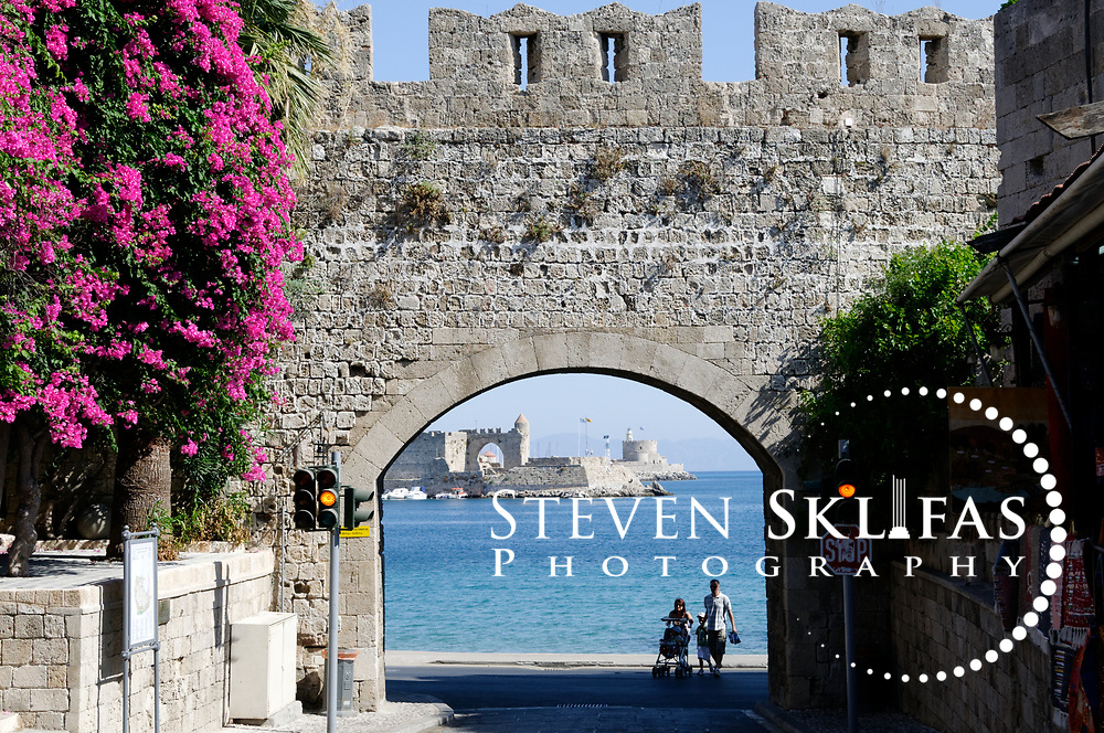 Rhodes. Greece.  St Catherine's Gate at the old town of Rhodes with ruins of St Paul's gate and port of Rhodes in background. The old town is a UNESCO world heritage listed site and the best preserved, oldest and largest living medieval city in Europe. The 4km defensive walls were built by the Knights of St John during the 13th to 15th century to defend Western Europe against the expanding Ottoman Empire. Within the walls are a medieval warren of small alleyways and magnificent historical buildings. The island of Rhodes is the largest of the Dodecanese Island group and one of the most popular Greek Islands.