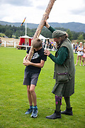 Highland Games, 3rd of August 2019, Newtonmore, Scotland, United Kingdom. A young boy struggles to lift his caber in the caber tossing competion. The Highland Games is a traditional annual event where competitors compete as strong men, runners, dancers, pipers and at tug-of-war. The games go back centuries and are happening through-out the summer across Scotland. The games are both an important event locally and a global tourist attraction.