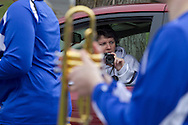 Middletown, New York - A woman sitting in a car gets ready to photograph children and adults marching in the 60th annual Middletown Little League parade on April 14, 2013.