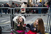 Girls waiting to see their favourite movie stars outside the BAFTA Awards ceremony in London, England, United Kingdom. Izzy and Bella do their make up while they wait under blankets in the cold. Izzy has a red rose she hopes to give to Leonardo DiCaprio. (photo by Mike Kemp/In Pictures via Getty Images)