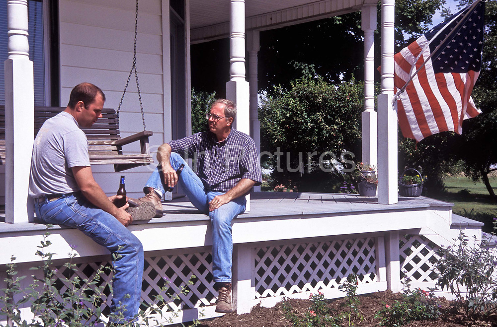 Two farmers take a break from work, drinking beers on the porch of home, Illinois, USA